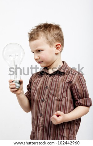 A child holding a large bulb. He is enraged because he did not have any interesting idea. - stock photo