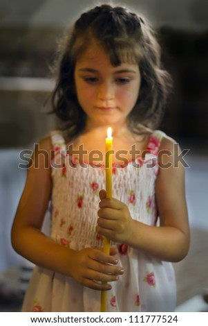 A child holds a candle in hands, focus on candle - stock photo