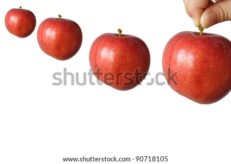 A child holds a large red apple fruit stem and wants to put him last among the other three, in isolation - stock photo