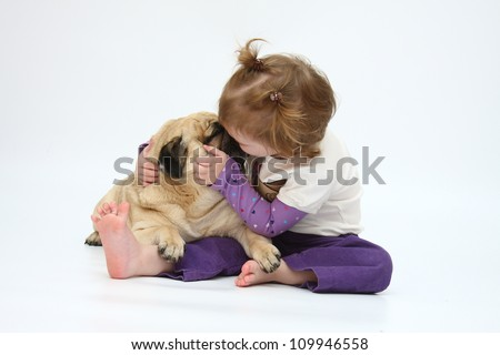 A child hugs and kisses pug dog breed - stock photo