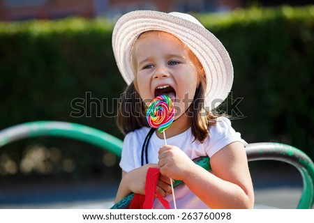 A child in a white hat licks a big colorful lollipop. Shallow depth of field. Focus on the model's face. - stock photo