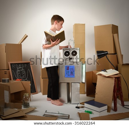 A child is reading a book and building a metal robot from cardboard boxes on white for an imagination, science or education concept. - stock photo