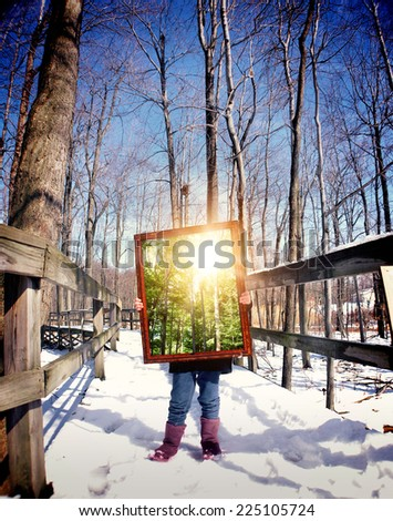 A child is standing on a winter trail in the woods holding a wooden frame with a picture of the summer with sunshine for a season concept.  - stock photo