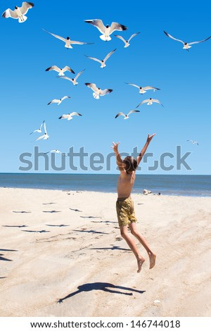 A child jumps towards flying seagulls. Focus on the boy - stock photo