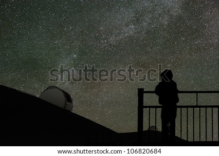 A child looks at the night sky with the Milky Way and a telescope dome on the horizon. - stock photo