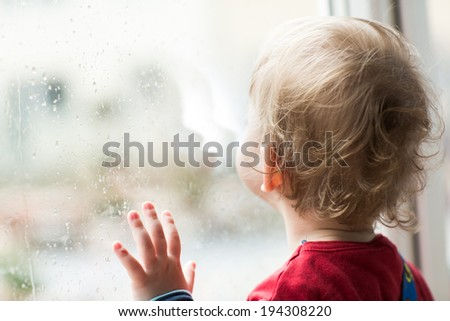 A child looks out the window - stock photo
