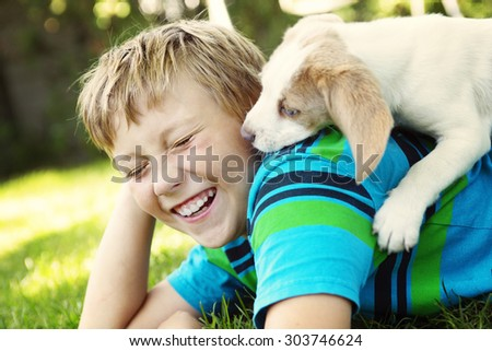 A Child lovingly embraces his pet dog - stock photo