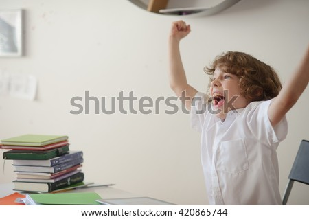 A child of primary school age do homework. School student has bothered to be engaged. He is indignant. - stock photo