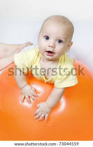 A child on a big orange ball - stock photo