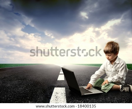 a child on the street with a laptop