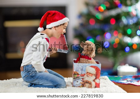 a child opening a christmas gift box with a puppy inside - stock photo