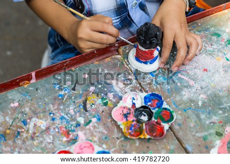 A child paints the colors of white plaster doll toys on the table - stock photo