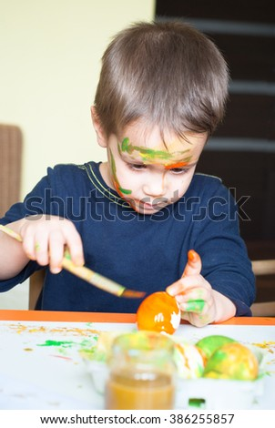 A child paints the eggs for Easter.