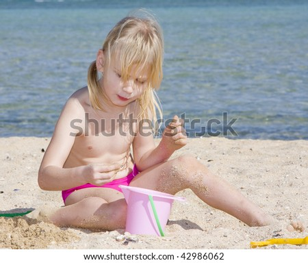 A child playing in the sand of the sea - stock photo