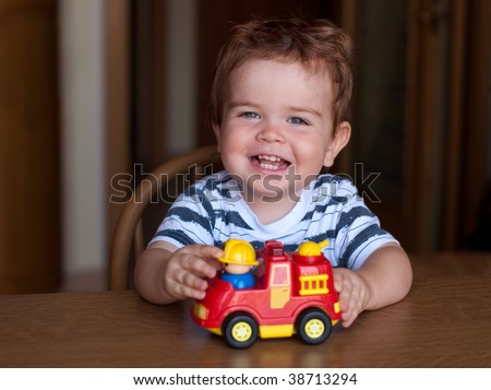 "a child playing with a ""fire"" car"