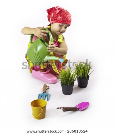 A child plays in the gardener. Watering seedlings