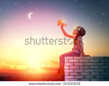 a child plays with a toy airplane in the sunset and dreams of becoming a pilot - stock photo