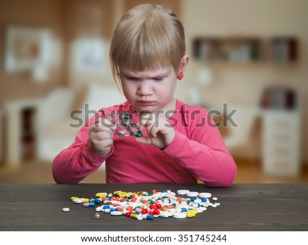 A child plays with pills. Girl gets pill capsule from the blister. Danger game with medication, pills. Risk of poisoning baby - stock photo