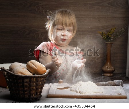 A child plays with the flour. Girl knead the dough. Girl funny stained with flour. Very fun game girl happy - stock photo