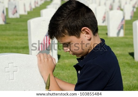 a child praying at a gravesite at a national cemetery in San Diego,CA on Memorial Day. - stock photo