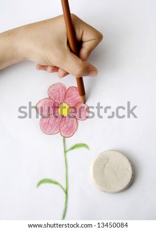 A child's hand drawing a moon-flower
