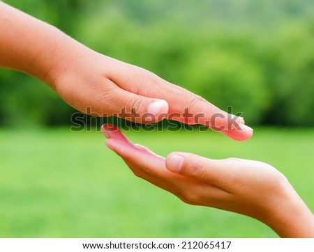 A child's hand on a background of green grass.