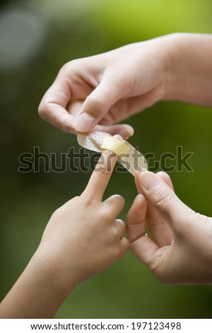 A Child'S Hand On Which A Band Aid Is Put