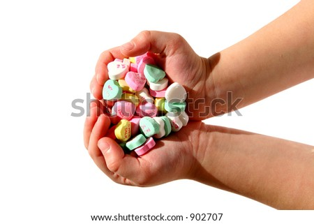 A child's hands full of candy hearts. - stock photo