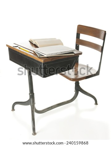A child's old school desk with books and a pencil on top.  On a white background. - stock photo