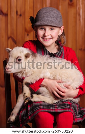 A child sits on a chair and on her lap favorite lamb On the farm - stock photo