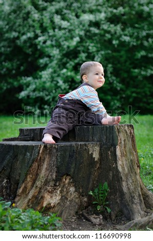 A child sits on a large tree stump with bare feet. Sunny summer day - stock photo