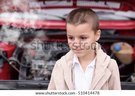 a child standing next to the car failing from which goes smoke and steam