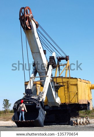 A child stands in the old excavator bucket without tracks - stock photo