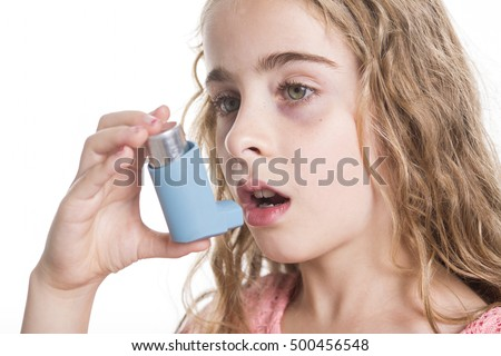 A child using inhaler for asthma. White background studio picture.
