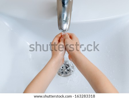 A child washing her hands in a sink with running water - stock photo