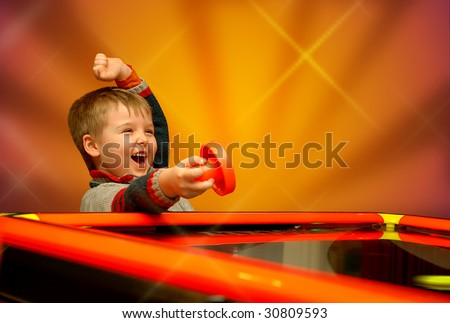 A child who has won his air hockey game, with a red mallet in his hand. - stock photo