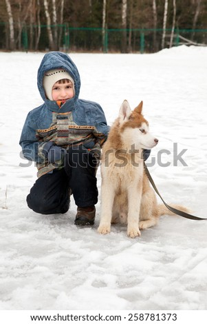 a child with a dog on a walk