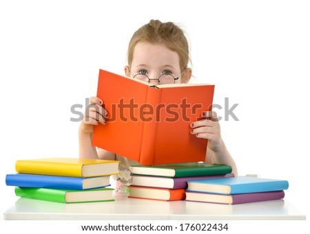 A child with glasses is sitting at a table in front a pile of books reading.