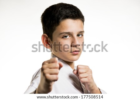 A child with his fist up in a karate fight stance. - stock photo