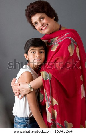 A child with his grandmother against a gray background