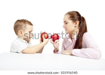 A child, woman and apples. The boy and woman sit facing each other and compare the fresh, red apples. - stock photo