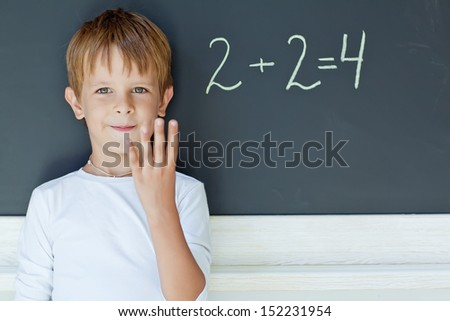 A child writes on the blackboard - stock photo