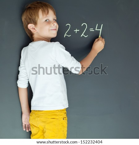 A child writes on the blackboard - stock photo