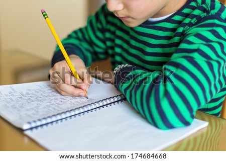 a child writing cursive - stock photo
