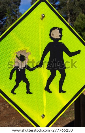 A children crossing road sign with bullet holes through the children's heads. The sign can be illustrative of school shootings as well as vandalism. - stock photo
