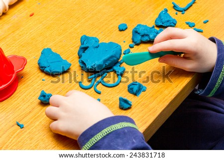 A Childs hands playing with Play Doh - stock photo