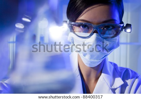A Chinese Asian female medical or scientific researcher or doctor looking at a flask of clear liquid in a laboratory. - stock photo