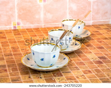 A chinese porcelain cups of tea with saucer and silver teaspoons are on the multicolor table - stock photo