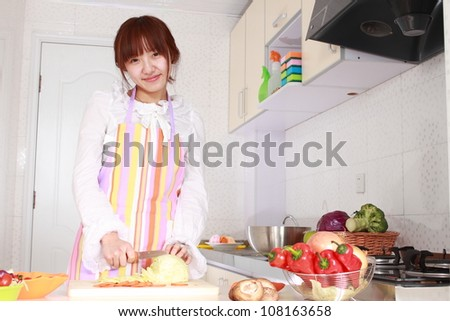 A Chinese woman is cooking on a chopping block with various kinds vegetable.