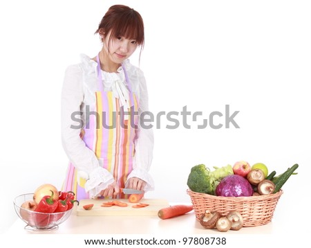 A Chinese woman is cooking  with various kinds vegetable. - stock photo